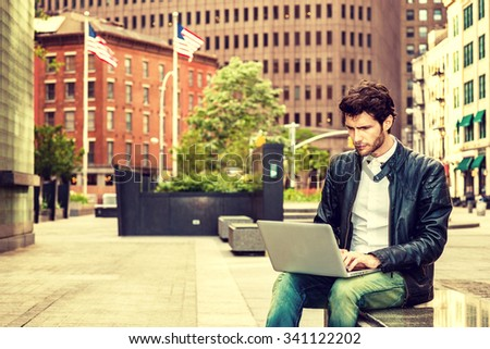 European businessman traveling, working in New York. Wearing leather jacket, jeans, a young guy with beard, sitting on marble bench on street, reading, working on laptop compute. Retro filtered look.