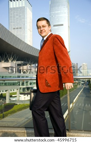 European businessman walking, holding briefcase in his hand, wearing red suit and blue tie. Elegant and handsome young man.