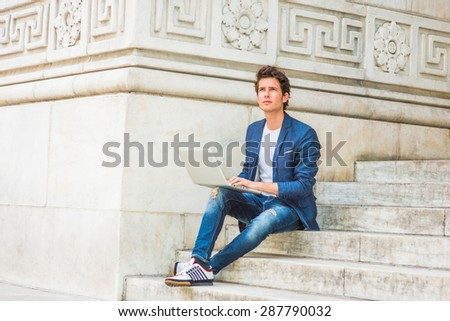European college student studying in New York. Wearing blue blazer, jeans, sneakers, a young guy sitting on stairs on campus, reading, thinking, working on laptop computer, confidently looking up. - stock photo
