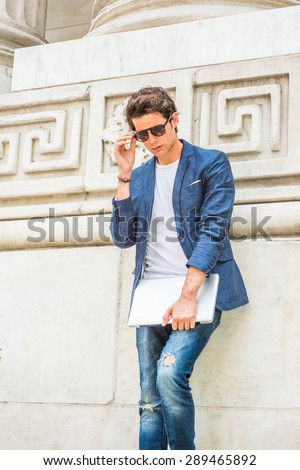 European college student studying in New York. Wearing blue blazer, white under shirt, jeans, sunglasses, holding laptop computer, a young guy standing by column on campus, looking down, thinking. - stock photo