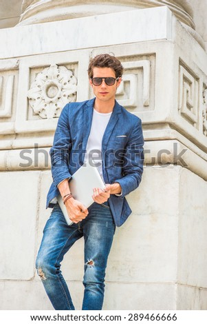 European college student studying in New York. Wearing blue blazer, white under shirt, jeans, sunglasses, holding laptop computer, a young guy standing by column on campus, looking at you, thinking. - stock photo