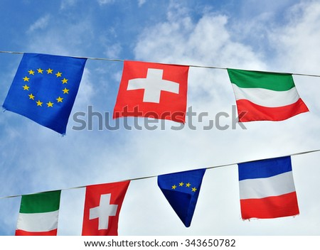 European countries symbols in the sky: french, italian, swiss and EU flags. - stock photo