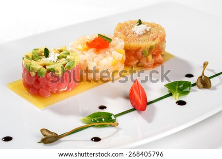European cuisine. Tartar with tuna fish, avocado, salmon and caviar decorated with strawberry and capers - stock photo