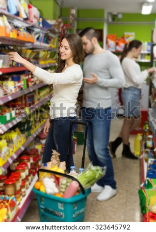 european customers standing near shelves with canned goods at shop