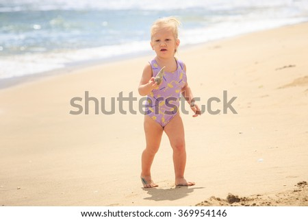 European cute little blond girl in swimsuit stand on beach against wave surf - stock photo