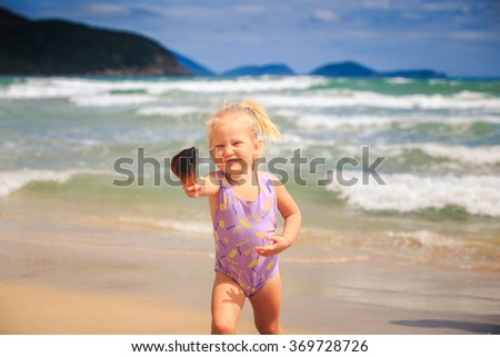 European cute little blond girl in swimsuit with pigtail shows nice shell smiles by foamy wave surf - stock photo