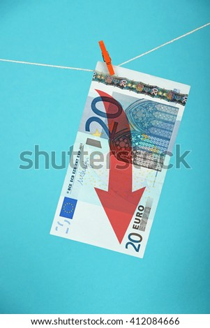 European economy crisis, decline of Euro currency, twenty Euro banknote with red arrow down hanged descending with pin at rope over blue background - stock photo