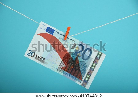 European economy crisis, decline of Euro, twenty Euro banknote with red arrow down hanged descending with pin at rope over blue background - stock photo