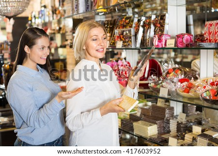 european female friends selecting bars of fine chocolates at confectionery display