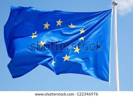 European flag in front of bright blue sky.