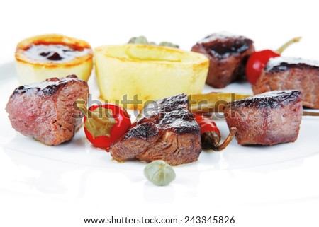 european food: grilled beef meat on white china plate isolated on white background hot pepper, capers and sauces - stock photo