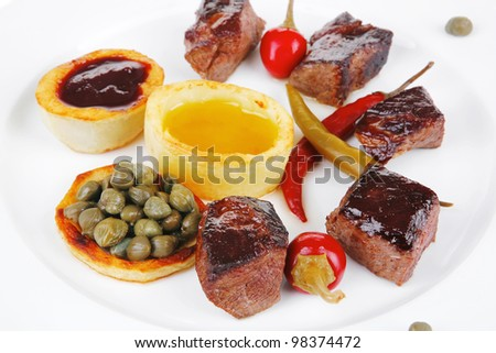 european food: roast beef meat goulash over white plate isolated on white background, with hot pepper, capers and sauces - stock photo