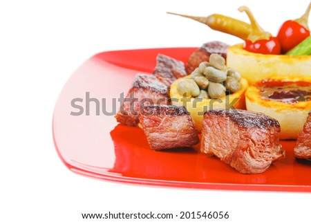 european food: roast beef meat over red plate isolated on white background with hot peppers, capers , olives oil , and bbq sauce . shallow dof - stock photo