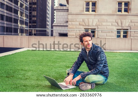 European graduate student studying in New York. Wearing black leather jacket, blue jeans, boot shoes, young guy with beard, crossing legs, sitting on green lawn, working on laptop computer, thinking. - stock photo