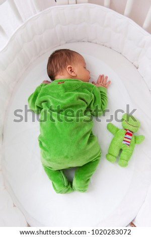 European kid in green overalls asleep in white baby cot