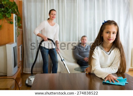 European little daughter helping mother to clean, father resting on couch - stock photo