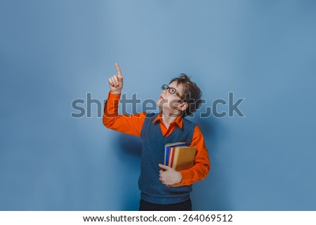 European-looking  boy of  ten  years  in glasses  thumbs up, the idea of the book on a blue background