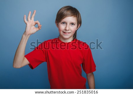 European-looking boy of ten years thumbs up gesture okay on a gray background - stock photo