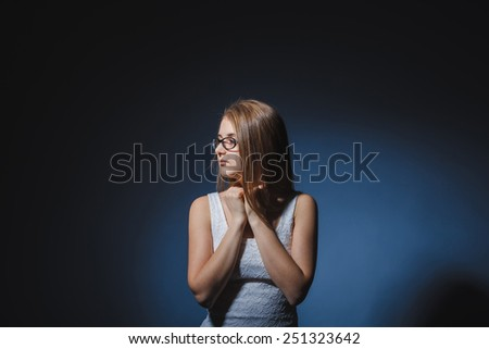 European-looking girl of twenty years of sadness, loneliness on a gray background - stock photo