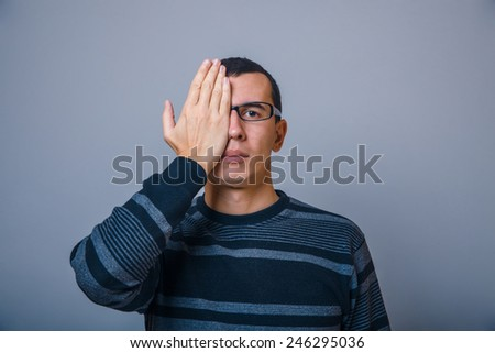 European-looking male put his hand over half of the face on a gray background - stock photo