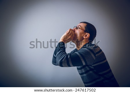 European-looking male put his hands to his mouth, shouting on gray background cross process - stock photo
