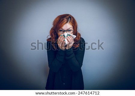 European-looking woman of about thirty redhead blowing his nose into a handkerchief on a gray background cross process - stock photo