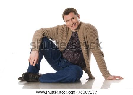 European man in everyday clothes sitting on white background - stock photo