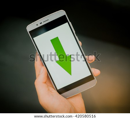 European mans hand holding new silver smartphone on the black background. Download sign is on the screen.