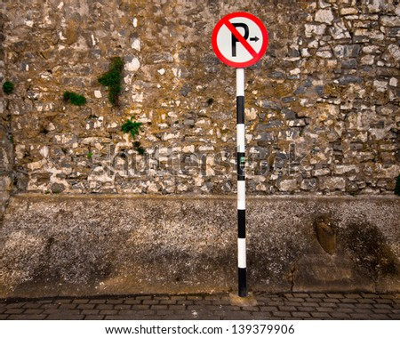 European no parking sign against rough stone wall - stock photo