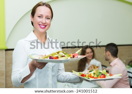 European positive waitress with plates and young couple at table indoor - stock photo