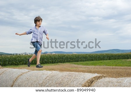 European school-age boy runs through the haystacks in a field in the sky - stock photo