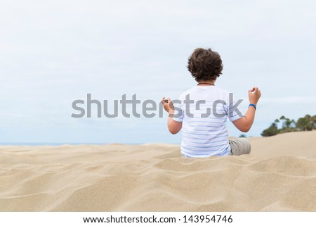 European school-age boy sitting in the lotus position on a sandy dune - stock photo