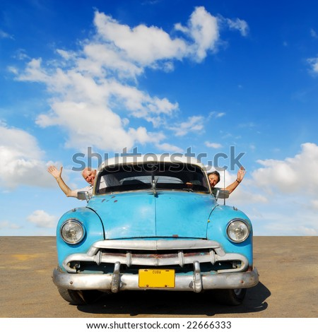 European senior couple having fun touring around Cuba, in an blue vintage oldtimer car - stock photo