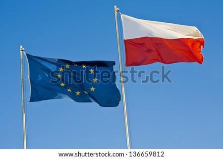 European Union flag and a Polish flag on a background of clear sky - stock photo