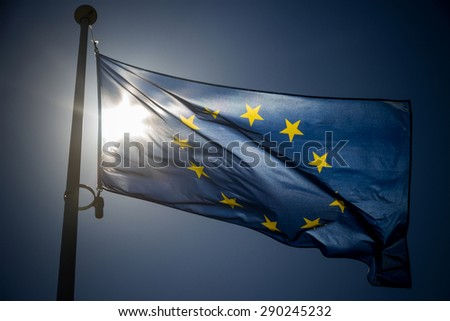 European Union flag on blue sky background, backlighting - stock photo