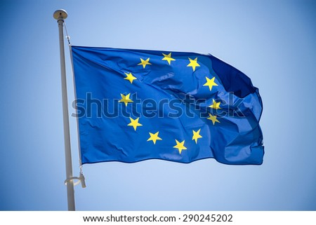 European Union flag on blue sky background, close up - stock photo