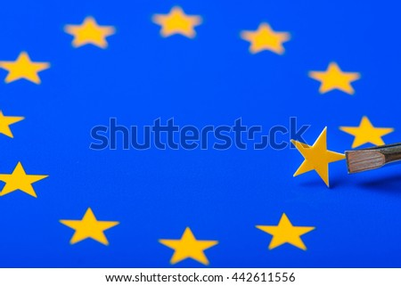 European Union flag with one star removed and hold in tweezers. Concept of Brexit as Britain vote to leave.