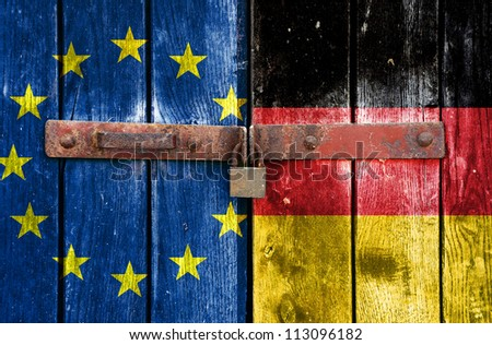 European Union flag with the Germany flag on the background of old locked doors - stock photo