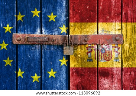 European Union flag with the Spain flag on the background of old locked doors - stock photo