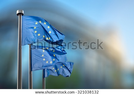 European Union flags in front of the blurred European Parliament in Brussels, Belgium - stock photo
