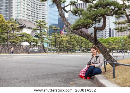 European woman a tourist with camera sitting in garden of Tokyo Imperial Palace, Japan. Copy space - stock photo