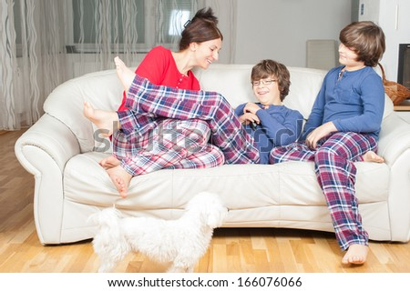 European woman with sons in pajamas on the couch, next to a small white dog - stock photo