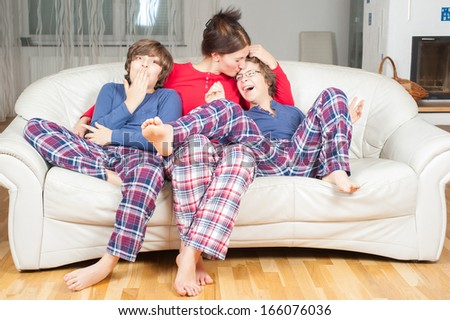 European woman with two sons in their pajamas on the couch