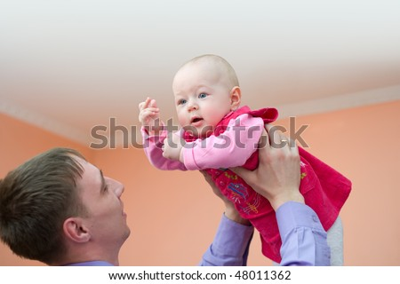 european young man holds his baby daughter above himself