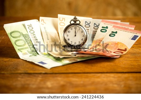 Euros and a pocket watch on a wooden table  - stock photo