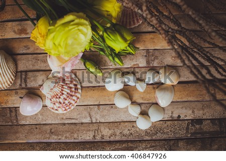 eustoma and  seashells in the shape of heart lying on a wooden board in a beautiful rustic style