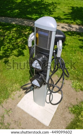 EV charger on green grass lawn. EV - electric vehicle charging station. Electric car charging point. - stock photo