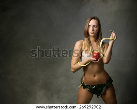 eve with snake and apple, dark and foggy room - stock photo