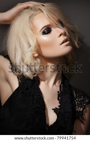 Evening and night style. Beautiful blond woman model in lacy black dress, with dark gloss make-up - stock photo