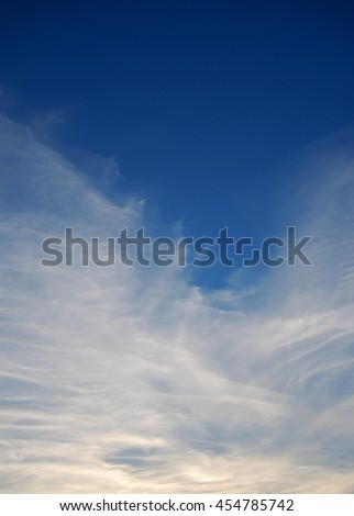 Evening blue sky with white cirrus clouds